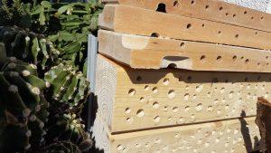 Insektenhotel aus alten Balken und einem aus dem Leim gegangenen Holzbrett.