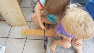 Die Kinder sägen die Seitenstücke zurecht.